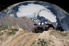 Off road driving arround the world. Four wheel car drivingout of a sand pit on the planet earth Royalty Free Stock Image