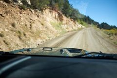 Off road driving in a jeep in Flat Tops. National Park, Colorado with a first person point of view through the windscreen of a dirt road and trees Royalty Free Stock Photography