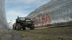 Off-road expedition car Toyota Land Cruiser driving on mountain road in snow tunnel surrounded by high snowdrifts. KAMCHATKA PENINSULA, RUSSIAN FAR EAST - JUNE stock video