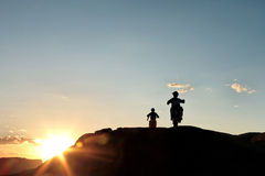 Off road motor bikers at sunset. Motor bikers silhouette with lens flare, on mountain trail at sunset in Moab, Utah Royalty Free Stock Photography