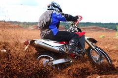 Off-road motorbike cornering in dirt. Off-road motorbike extreme cornering. Motion blur with flying dirt Royalty Free Stock Photos