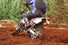 Off-road motorbike cornering in dirt. Off-road motorbike extreme cornering. Motion blur with flying dirt Stock Photos