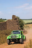 Off road motorsport. St WULSTAN, UK - JULY 21: An unnamed driver competing in the AWDC UK Comp Safari championship speeds through the ruined barn and gate Royalty Free Stock Photo