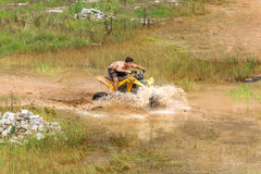 Off road on 4x4 quad bike through mud puddle Stock Photo