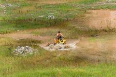 Off road on 4x4 quad bike through mud puddle Royalty Free Stock Photo