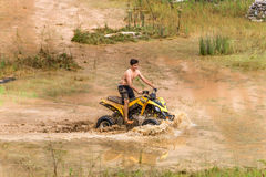 Off road on quad bike rally over mud puddle Royalty Free Stock Images
