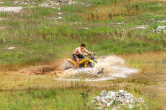 Off road on quad bike rally over mud puddle Royalty Free Stock Photography