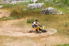 Off road on quad bike rally over mud puddle Stock Photos