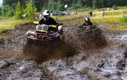 Off-road racing on ATV. An ATV spraying mud in a dirt road rally Stock Images