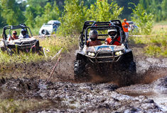 Off-road racing on ATV. An ATV sprays mud in a dirt road rally Royalty Free Stock Photo