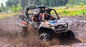 Off-road racing on ATV. An ATV sprays mud in a dirt road rally Stock Photos