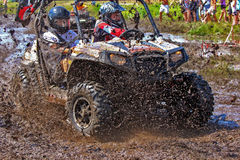 Off-road racing on ATV. An ATV sprays mud in a dirt road rally Royalty Free Stock Image