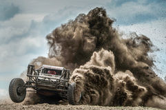 Off road racing. An off road race car throws up a plume of dust whilst competing in a race Royalty Free Stock Images