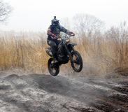 Off-road rider is jumping. Against a steaming ground Stock Image