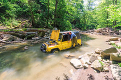 Off-road Russain car stuck in mountain river at breakdown while jeeping. Driver repairs auto with lifted hood. Sochi, Russia - June 9, 2009: Yellow off-road Stock Photography