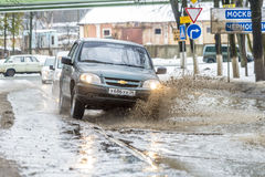 Off-road in Russia. The car rides on a deep puddle in the spring Stock Photography