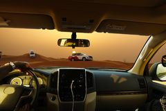 Off road safari with SUV vehicles in the desert at sunset, view from the car stock photos