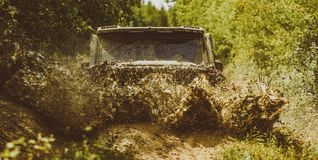 Off road sport truck between mountains landscape. Offroad vehicle coming out of a mud hole hazard. Drag racing car burns. Rubber. Extreme. Jeep crashed into a stock image