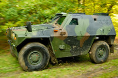 Off-road Truck. Military off-road vehicle driving on a forest dirt road, ripping leaves and small branches hanging over the road. Blurred wheels and vegetation Stock Image