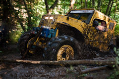 Off road truck in competition. Pickup 4x4 truck driving trough mudy track in motion with sprays of mud Stock Image