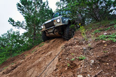 Off road truck in trial competition. Closeup of 4x4 truck driving downhill on the edge Stock Images