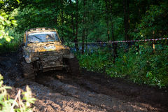 Off road truck in trial competition. Pickup 4x4 truck driving trough mudy track defocused, focus on mud and branches in front Royalty Free Stock Images