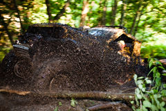 Off road truck in trial competition. Pickup 4x4 truck driving trough mudy track in motion with sprays of mud Stock Images
