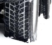 Off road truck wheels on the snow close up stock photo. Studless winter tire protector packed with snow detailed Stock Photos