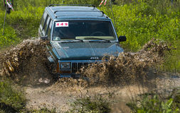 Off-road vehicle brand Jeep Cherokee overcomes a pit of mud Royalty Free Stock Photography