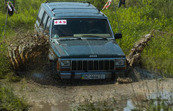 Off-road vehicle brand Jeep Cherokee overcomes a pit of mud Stock Images