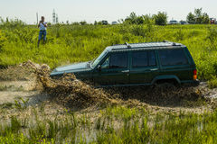 Off-road vehicle brand Jeep Cherokee overcomes a pit of mud Stock Image