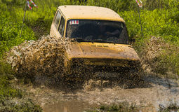 Off-road vehicle brand VAZ-NIVA overcomes a pit of mud Royalty Free Stock Photos