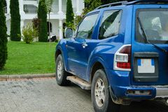 Off-road vehicle with broken tail lights, parked in front of the. Green lawn of the house stock image
