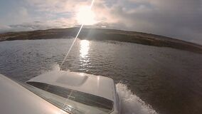 Off-road vehicle crossing an Iceland river with the sun facing