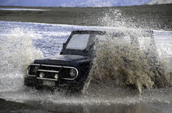 Off road vehicle crossing a river Stock Photos