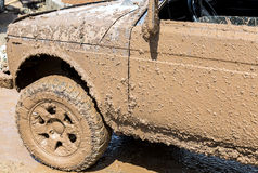 Off-road vehicle after driving in the rain. On extremely dirty rural road Stock Photos