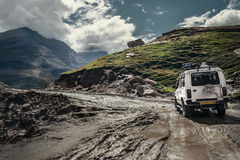 Off-road vehicle goes on the mountain way during the rainy seaso Royalty Free Stock Image