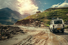 Off-road vehicle goes on the mountain way during the rainy seaso. N Royalty Free Stock Photos