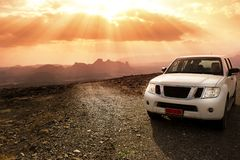Off-road vehicle on the Jebel Shams mountains and cloudy sky with amazing sunrays. An Off-road vehicle on the Jebel Shams mountains and cloudy sky with amazing royalty free stock image