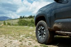 Off-road vehicle on a mountain track. With a low angle view of the front side and tire with scenic landscape behind Royalty Free Stock Photos