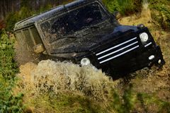 Off road vehicle or SUV crossing puddle with dirt splash. Competition, energy and motorsport concept. Car racing in. Off road vehicle or SUV crossing puddle with stock images
