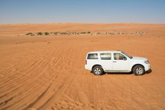 Off-road vehicle in the Wahiba Sand Desert and Bedouin camp in the background royalty free stock photo