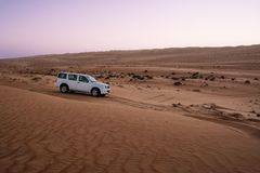 Off-road vehicle in the wahiba sands desert dunes at sunset Oman stock image