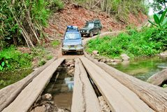 Off road vehicles are crossing the creek by a wooden bridge in the forest royalty free stock images