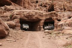 Off-road vehicles stand in amazing rainbow-coloured hollows of c. Aves in ancient city of Petra, Jordan royalty free stock image