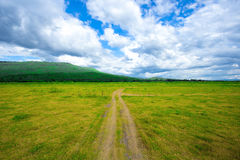 Off road way toward mountain surrounded by meadow grass field under beautiful clear blue sky. The off road way show tire trace fro Royalty Free Stock Image