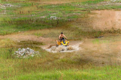 Off road on 4x4 quad bike through mud puddle Royalty Free Stock Photo