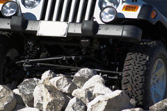 Off Roading. A closeup of a Jeep or four-wheeled vehicle climbing over large rocks and boulders on a hillside Stock Image