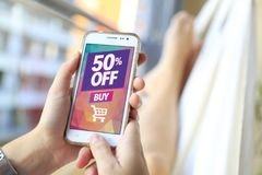 50% OFF Sale. Smartphone sale advertising. Internet publicity. 50% OFF Sale. Woman in a hammock with a smartphone with a 50% discount advertising on the screen stock photography