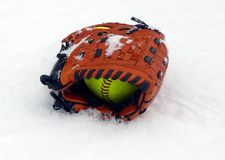 Off Season. Softball Glove and ball sitting in fresh snow Stock Image